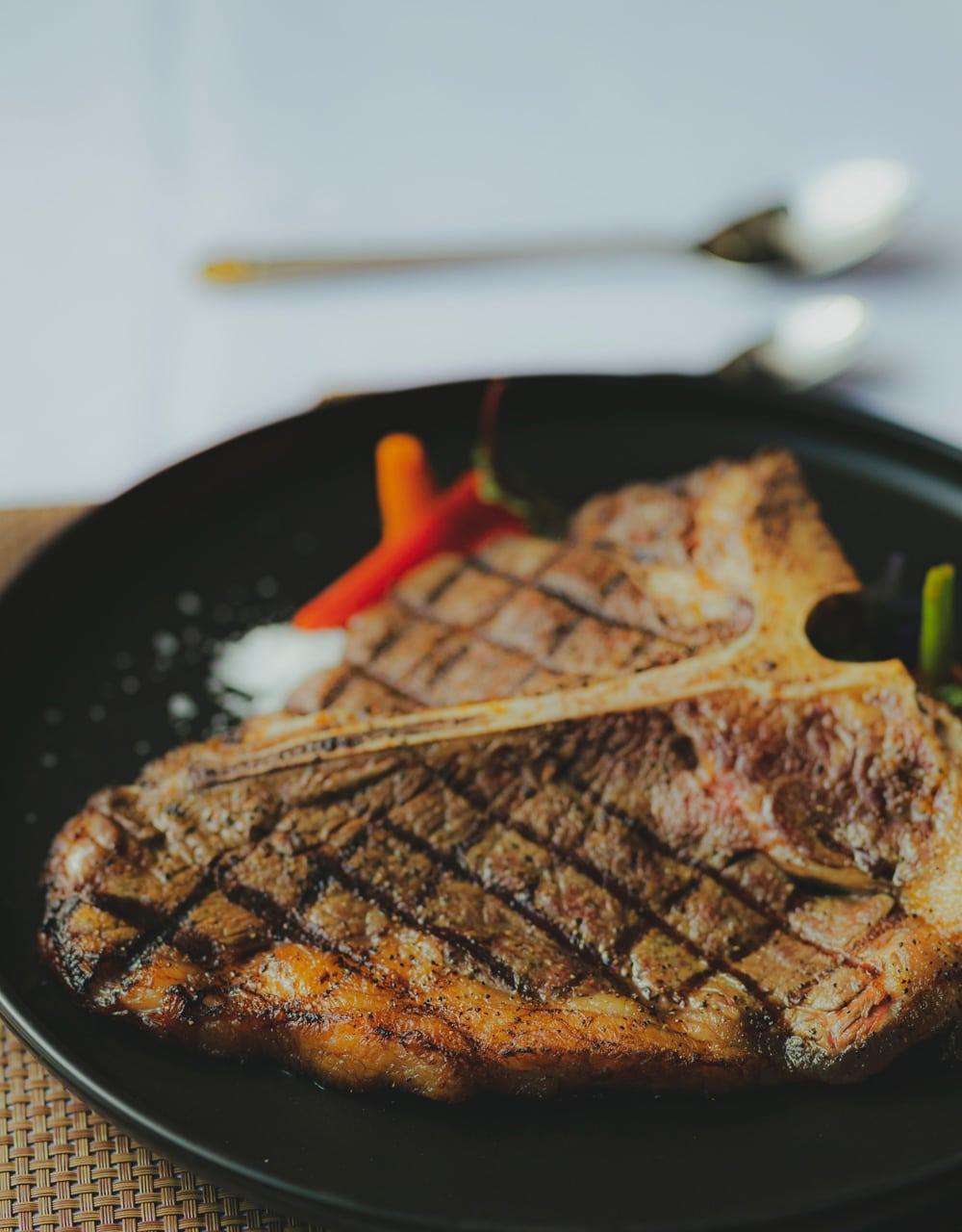 Bistecca alla fiorentina - ein gegrilltes Stück Porterhouse- oder T-Bone-Steak, Foto: Hanxiao / Unsplash